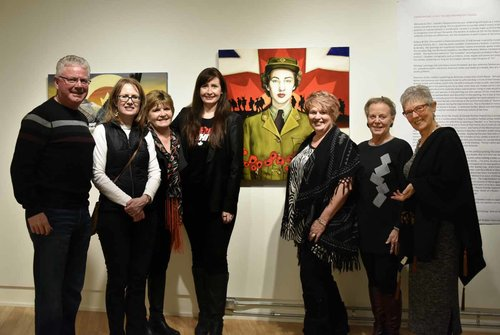 people posing with artist at art gallery