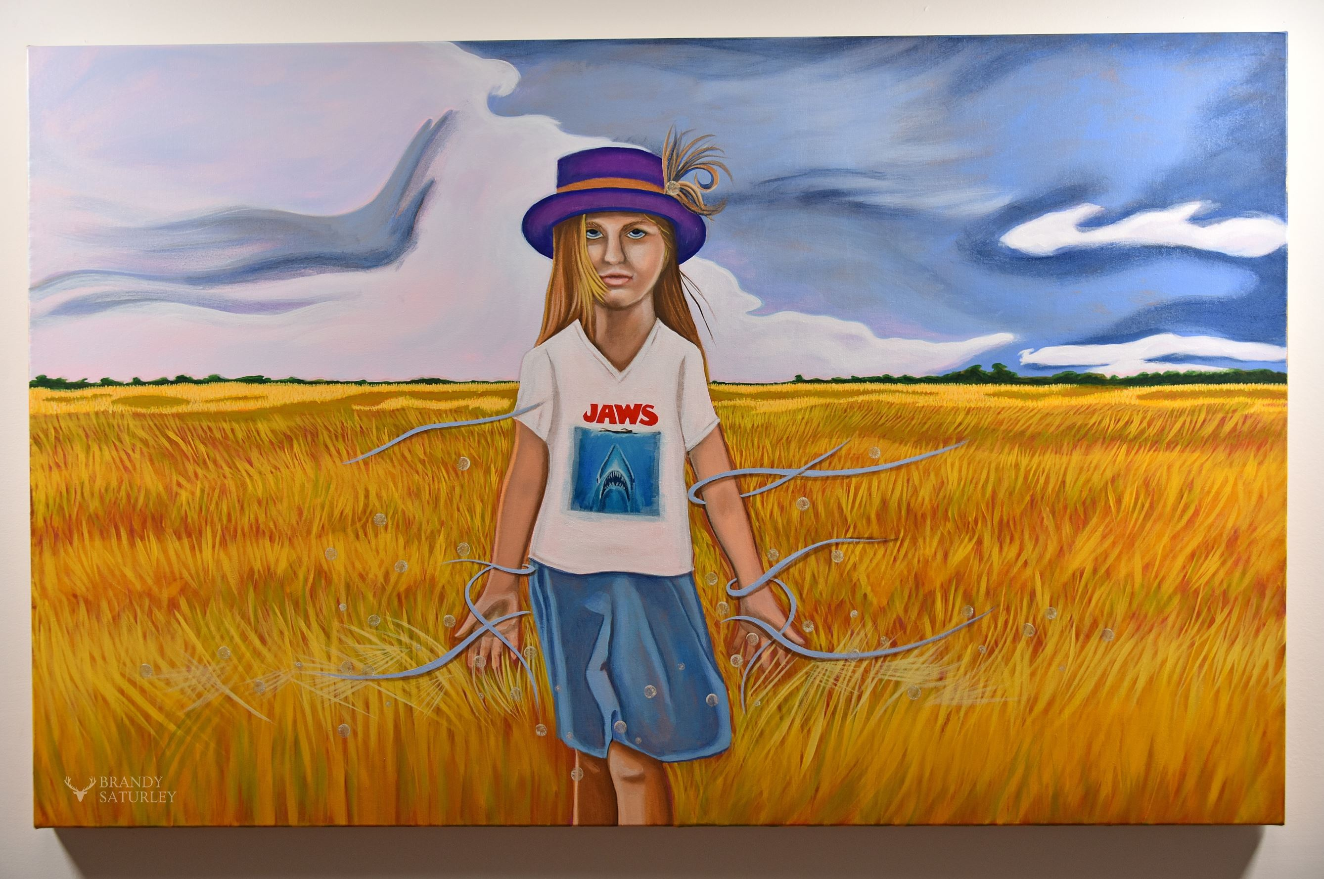 painting of girl wearing jaws t-shirt and purple hat walking through wheat fields Brandy Saturley
